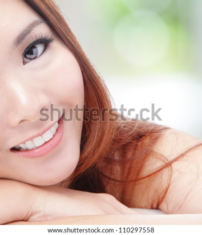 portrait of half face young woman smile with health teeth and charming smile on green background, mode is asian girl - stock photo