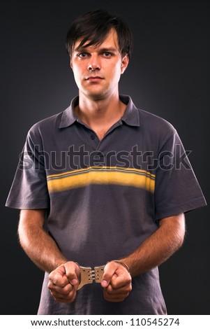 portrait of handcuffed man on gray backing - stock photo