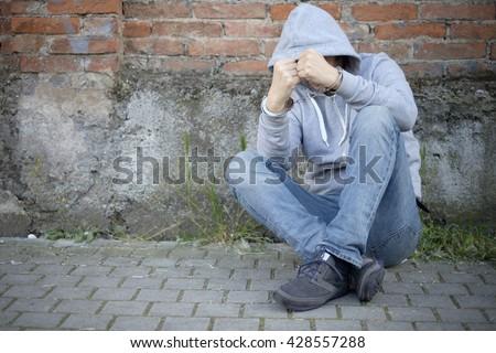 portrait of handcuffed man with face hidden by sweatshirt hood - stock photo
