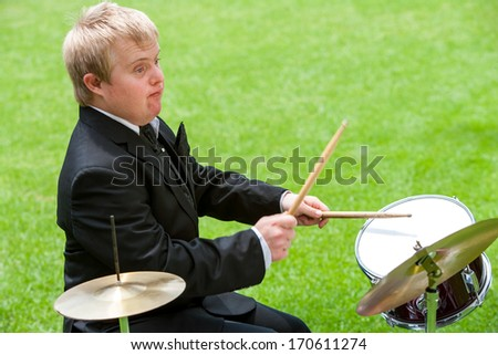 Portrait of handicapped drummer in suit playing outdoors. - stock photo