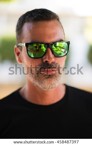 Portrait of handsome adult man in mirrored sunglasses
