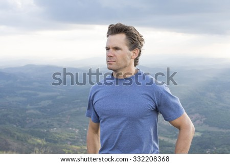 Portrait of handsome adventurous Caucasian man standing proudly on top of mountain overlooking valley under cloudy sky - stock photo