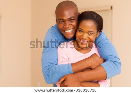 portrait of handsome african american man hugging his wife - stock photo