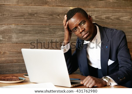 Portrait of handsome African banker using laptop for distant work while sitting at the cafe, having coffee during lunch break, looking at the camera with serious expression, resting elbow on the table