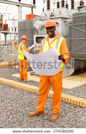 portrait of handsome african electric engineer with blueprint at substation - stock photo