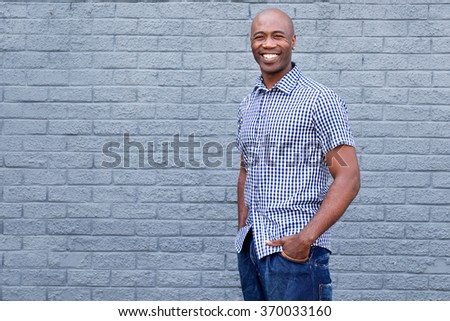 Portrait of handsome african man smiling against a gray wall - stock photo