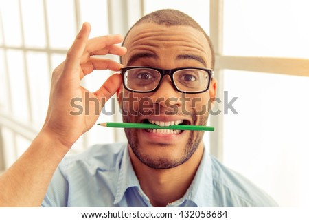 Portrait of handsome Afro American businessman in eyeglasses with pencil in his teeth looking at camera and showing faces - stock photo