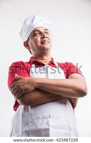 Portrait of handsome and cheerful Indian male chef in uniform with hands folded, isolated over white background, selective focus on eye,  copy space