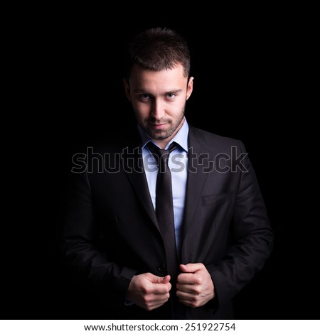 Portrait of handsome and young businessman on black background.