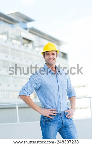 Portrait of handsome architect with hands on hips outdoors - stock photo