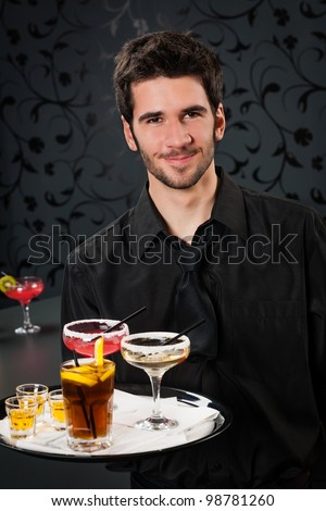 Portrait of handsome barman at bar holding tray with cocktails - stock photo