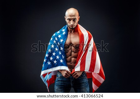 Portrait of handsome bearded bodybuilder in American flag looking at camera.Black background.Isolated.