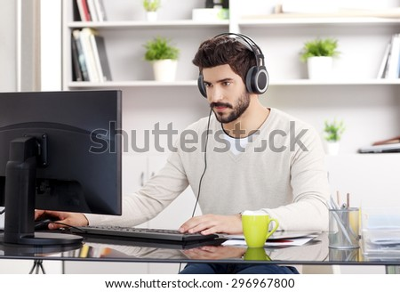 Portrait of handsome bearded graphic designer at workplace. Young creative worker sitting in front of computer and surfing on internet while listening music online at office.