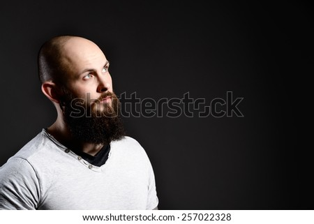 Portrait of handsome bearded man - dark background - stock photo