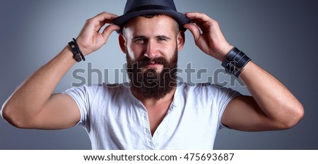 Portrait of handsome bearded man in hat standing , isolated on grey background