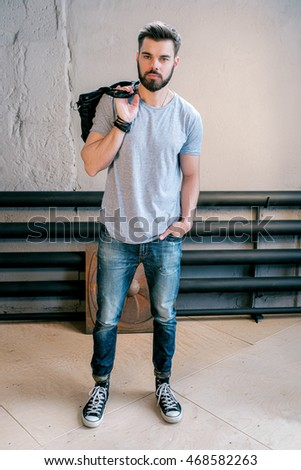 Portrait of handsome bearded man in stylish clothes with handbag against of old wall indoor