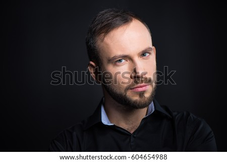 Portrait of handsome bearded man looking at camera  isolated on black