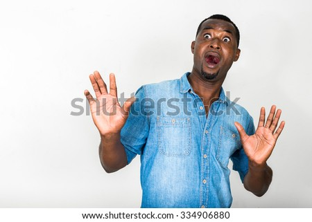 Portrait of handsome black African American man looking scared - stock photo