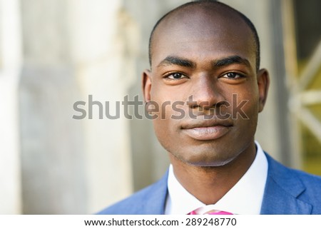 Portrait of handsome black man wearing suit in urban background - stock photo
