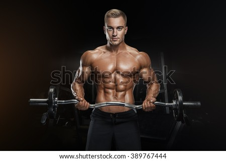 Portrait of handsome bodybuilder performing the biceps curl with EZ curl bar at gym. Perfect physique athletic young man with six pack, perfect abs, shoulders, biceps, lats and chest.  - stock photo
