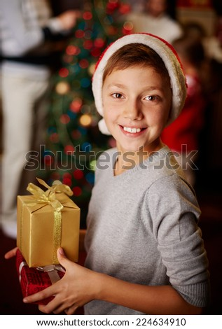 Portrait of handsome boy in Santa cap holding giftboxes - stock photo