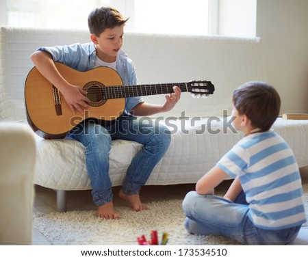 Portrait of handsome boy playing the guitar with his brother near by - stock photo