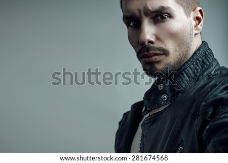 Portrait of handsome brutal bearded man in leather jacket. - stock photo