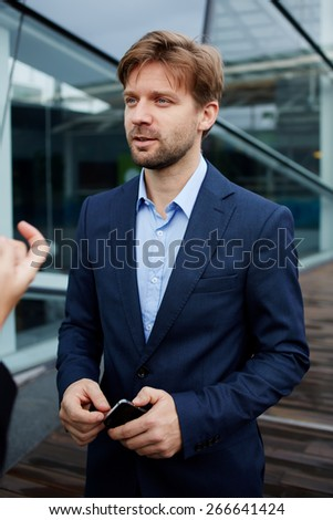 Portrait of handsome business man in suit talking to someone holding cellphone in the hands,young caucasian executive having conversation outside office during work break,colleagues having discussion - stock photo