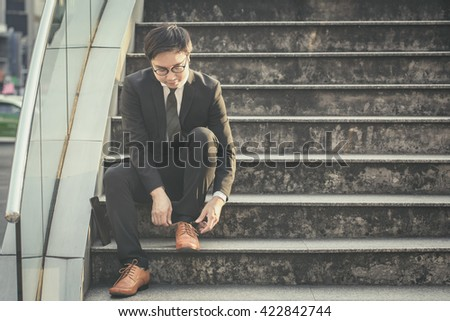 Portrait of handsome business man tie shoe on stair