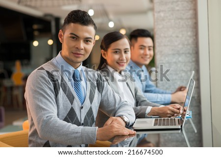 Portrait of handsome businessman and his colleagues sitting in the cybercafe and looking at the camera - stock photo