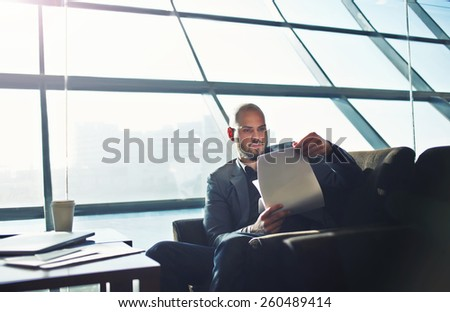 Portrait of handsome businessman examining paperwork in office interior, male executive studies documents or papers during his coffee time - stock photo