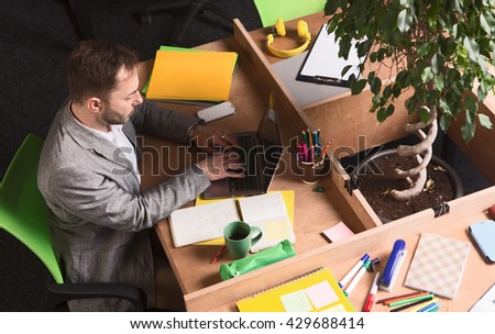 Portrait of handsome businessman in grey business suit working in office. Young man using laptop computer and typing something. - stock photo