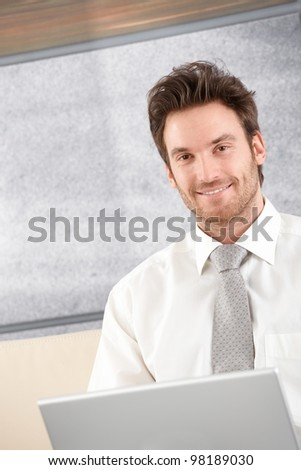 Portrait of handsome businessman sitting in elegant office, smiling. - stock photo
