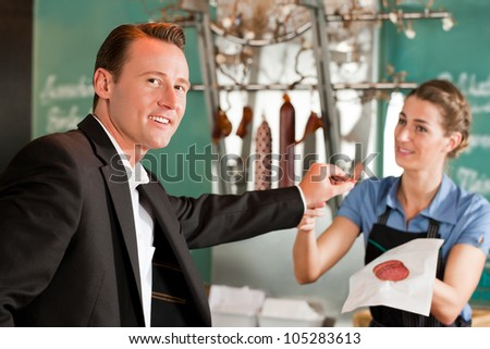 Portrait of handsome businessman smiling with butcher in background holding meat