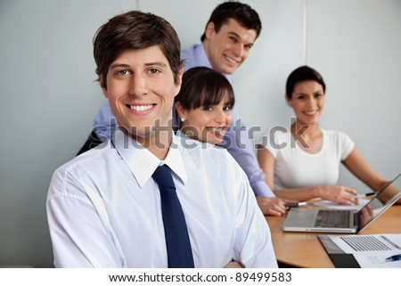 Portrait of handsome businessman smiling with team working in background - stock photo