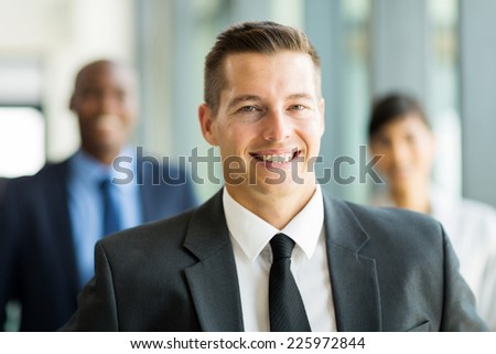 portrait of handsome businessman with colleagues on background - stock photo