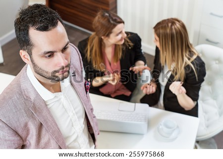Portrait of handsome businessman with two female colleague talking at background. - stock photo