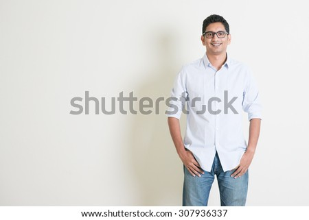 Portrait of handsome casual business Indian guy smiling, hands in pocket, standing on plain background with shadow, copy space at side.
