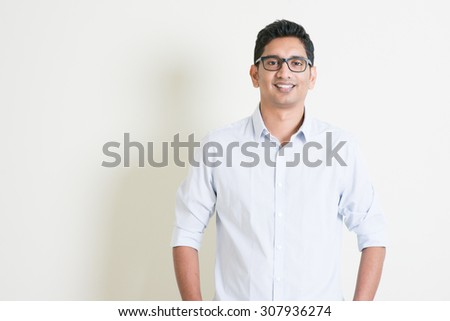 Portrait of handsome casual business Indian man smiling and looking at camera, standing on plain background with shadow, copy space at side.