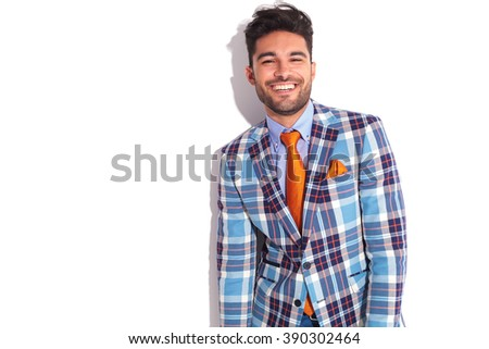portrait of handsome casual man in plaid jacket and orange tie, smiling at the camera in white studio background - stock photo