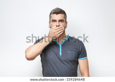 Portrait of handsome caucasian man with grey beard standing on white background. Man covering his mouth with hand - stock photo