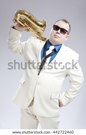 Portrait of Handsome Caucasian Saxophone Player With Music Instrument Over Shoulder. Posing Against White. Vertical Image Orientation - stock photo