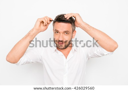 Portrait of handsome cheerful young man combing his hair