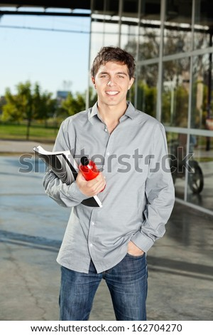 Portrait of handsome college student holding book and juice bottle on campus - stock photo