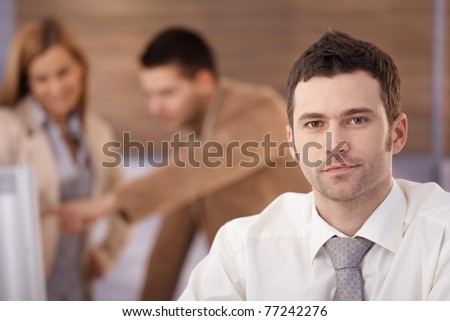 Portrait of handsome confident businessman sitting in office, colleagues talking in background.? - stock photo