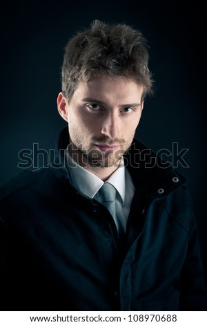 Portrait of handsome, confident man against dark background. - stock photo