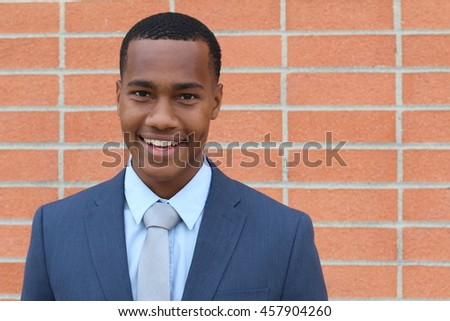 Portrait of handsome confident young African businessman smiling happy, looking at camera with copy space - stock photo