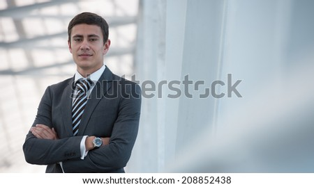 Portrait of handsome confident young businessman standing arms crossed, looking at camera. - stock photo