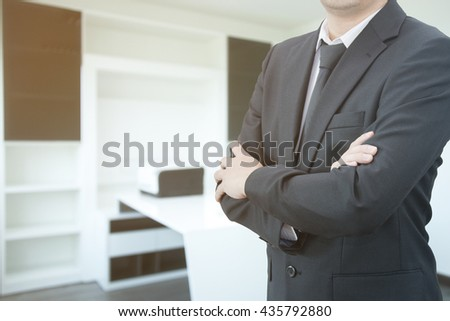 Portrait of handsome confident young businessman standing arms crossed with clean office background - stock photo