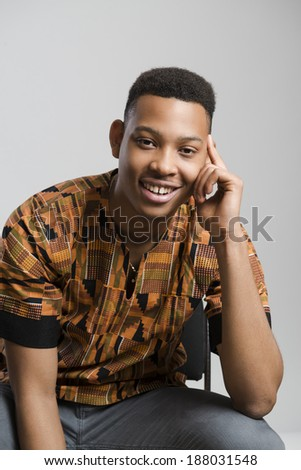 Portrait of handsome dark skinned male model smiling and wearing traditionally African clothes against white background - stock photo